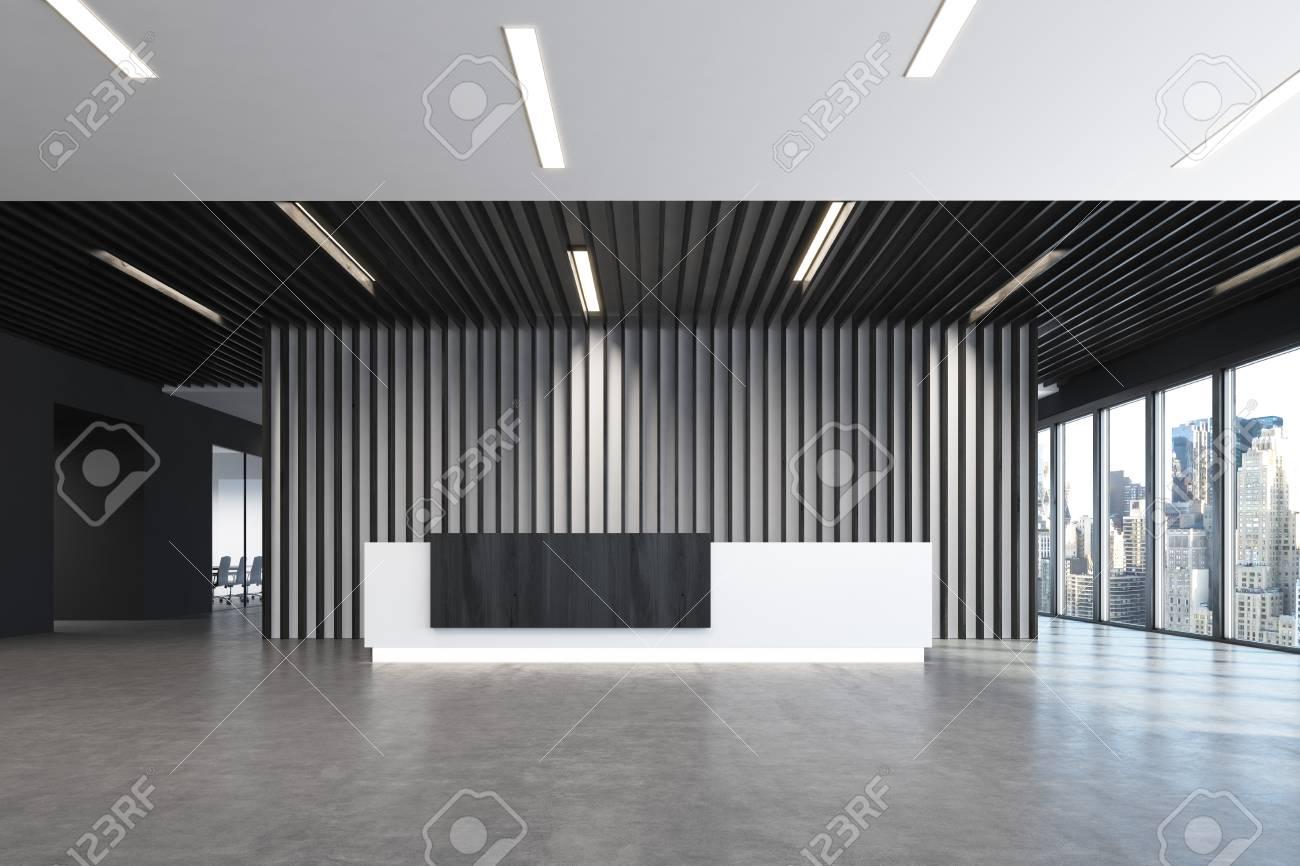 Comptoir de réception blanc et noir est debout dans un hall de