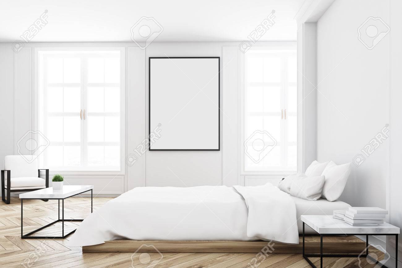 Vista di un interno bianco della camera da letto con un letto matrimoniale,  un tavolino da caffè, un muro bianco e un\'immagine verticale su di esso. ...