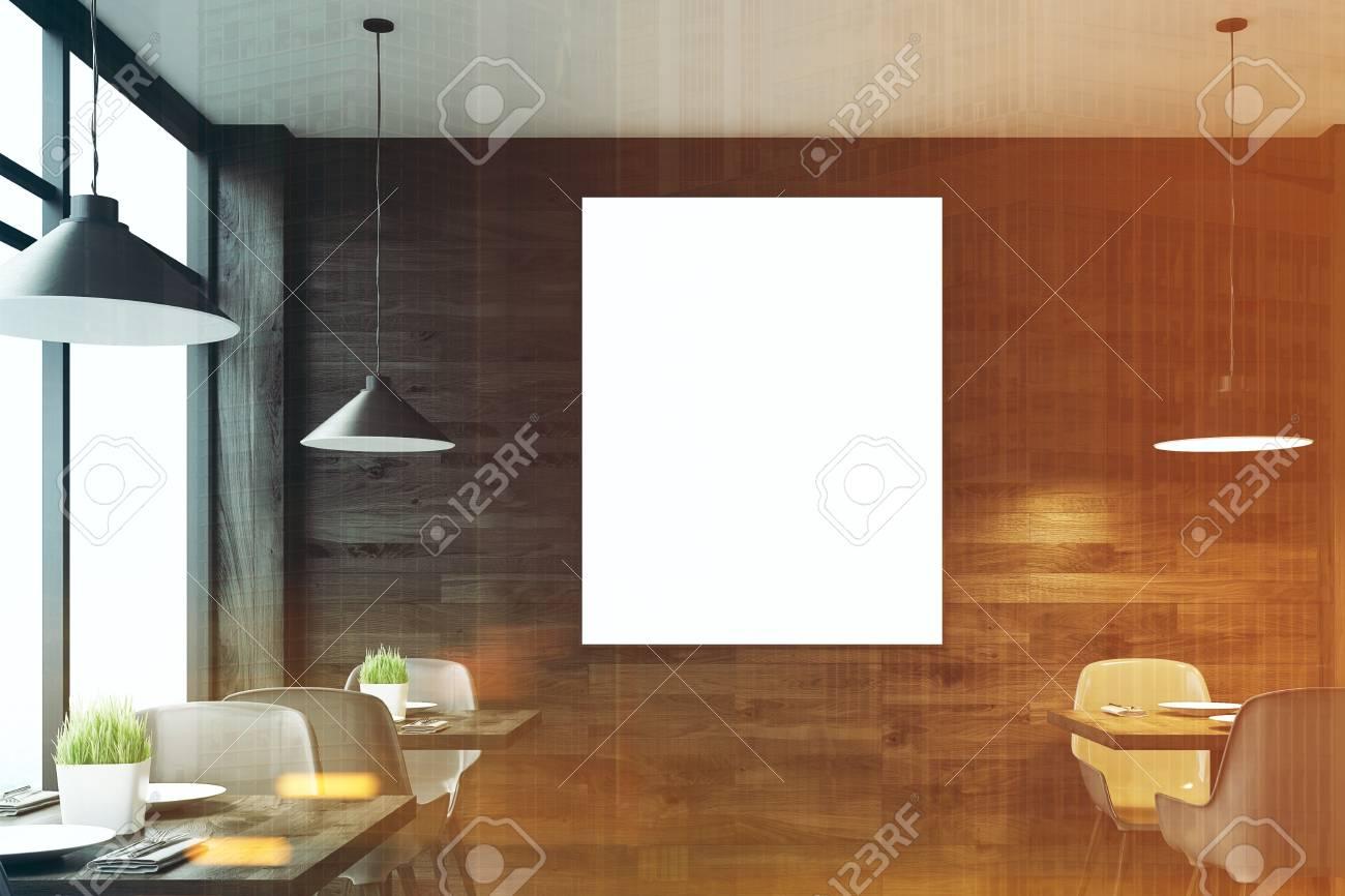 Vista frontale di un interno di caffè in legno scuro con tavoli quadrati, sedie bianche in piedi lungo una finestra panoramica e un poster verticale