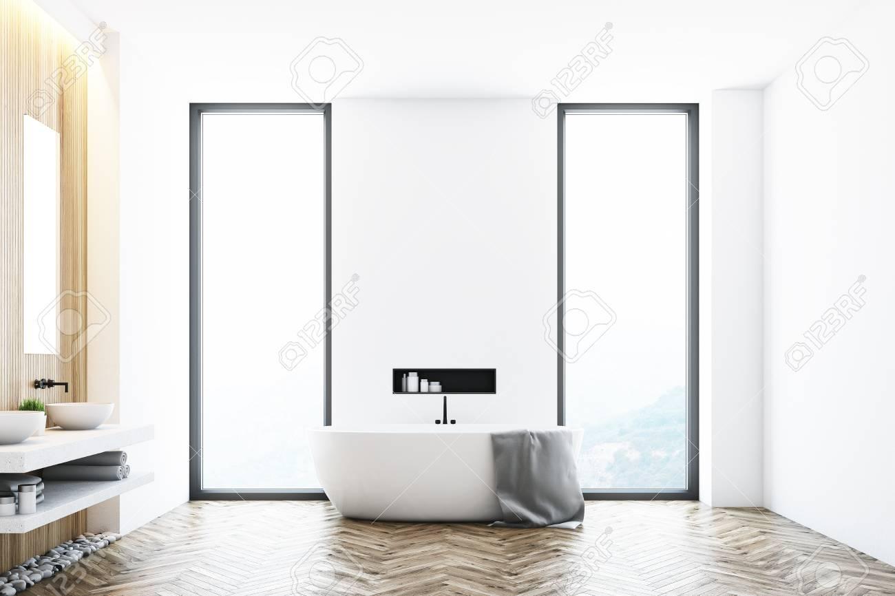 Intérieur de salle de bain moderne blanc avec une baignoire blanche debout  près d\'une fenêtre, une grande serviette suspendue sur le côté et une ...