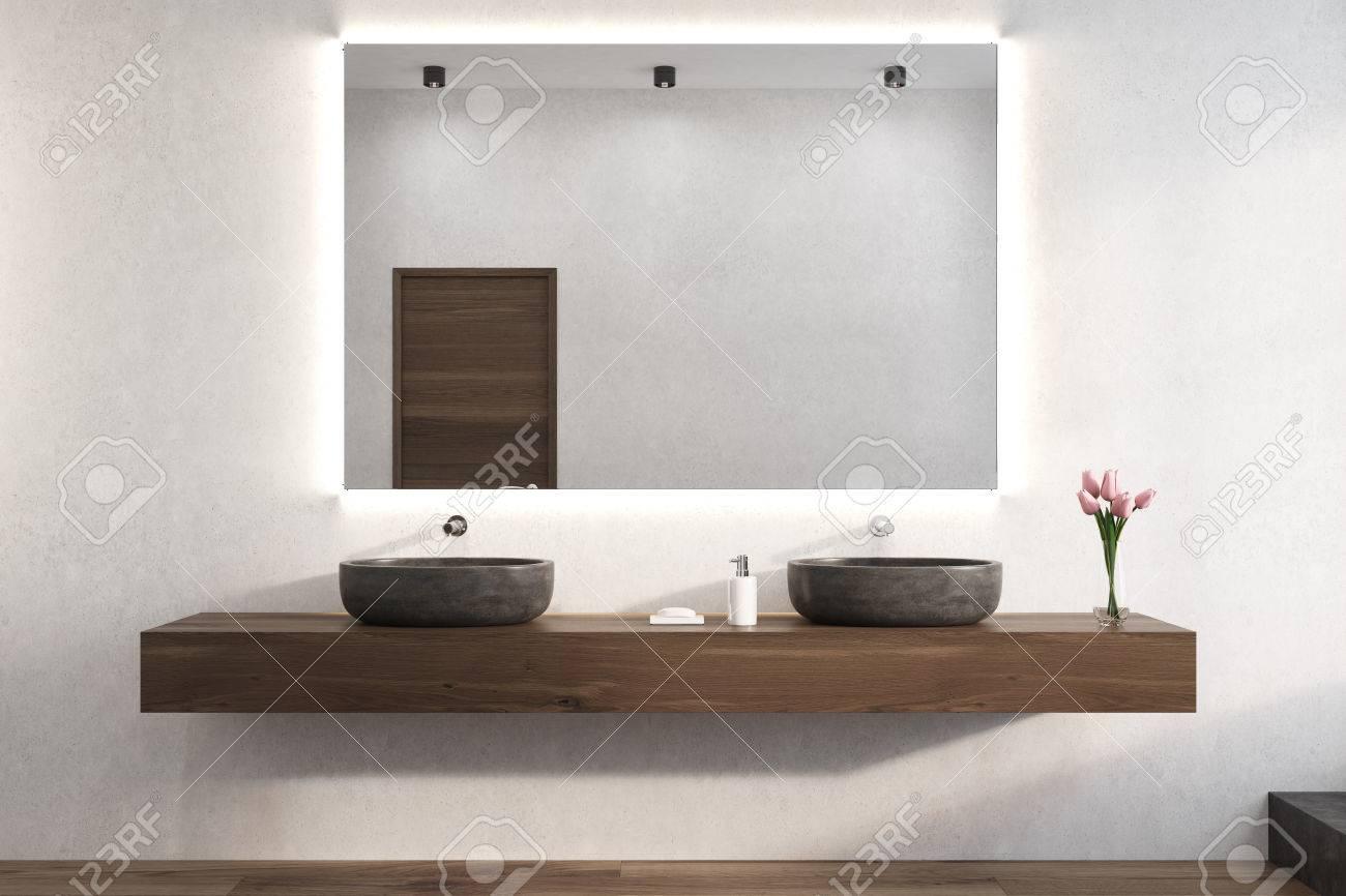 Il grande specchio orizzontale è appeso su una parete bianca del bagno. Ci  sono due lavandini su una mensola di legno sotto di essa e un vaso di ...