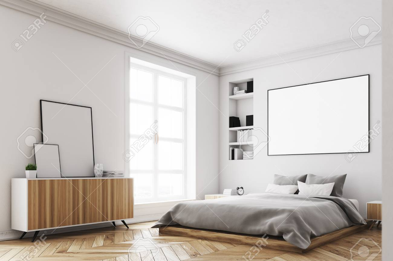 Corner of a modern luxury bedroom with white walls, a large bed..
