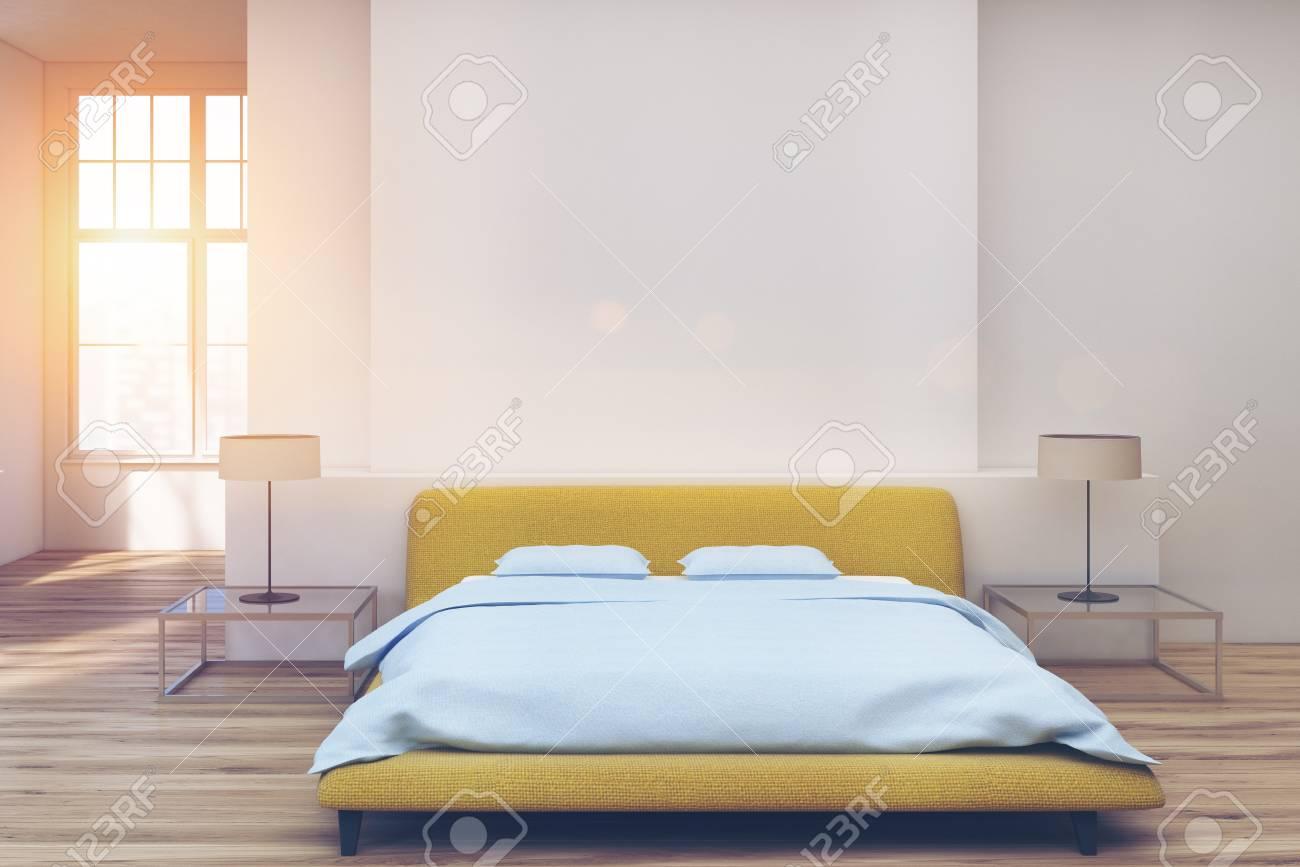 Chambre à coucher avec un lit double jaune au centre d\'une pièce avec un  sol blanc. Table de chevet en verre avec une lampe. Rendu 3D mock up image  ...