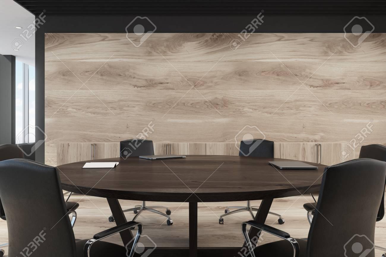 Bureau avec une grande table ronde noire, des chaises et des murs en bois  clair. Lobby avec des fenêtres panoramiques sur la gauche. Maquette 3D