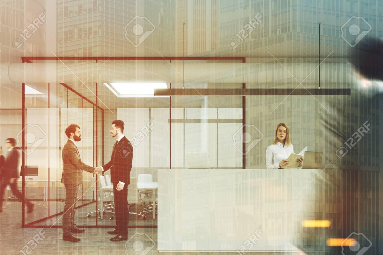 Personnes dans un hall de bureau moderne avec des murs gris et en