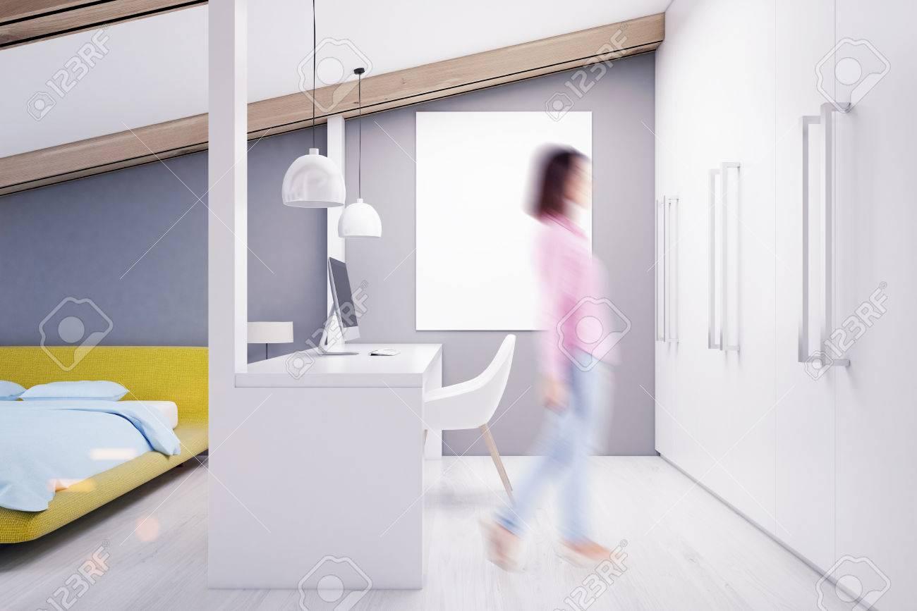 Femme dans une chambre mansardée grise avec un bureau à domicile