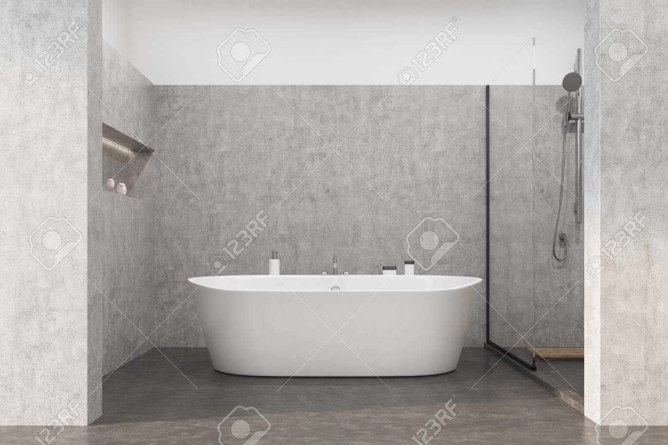 Gray Bathroom Interior With A Concrete Floor, A White Tub, A Shower And A
