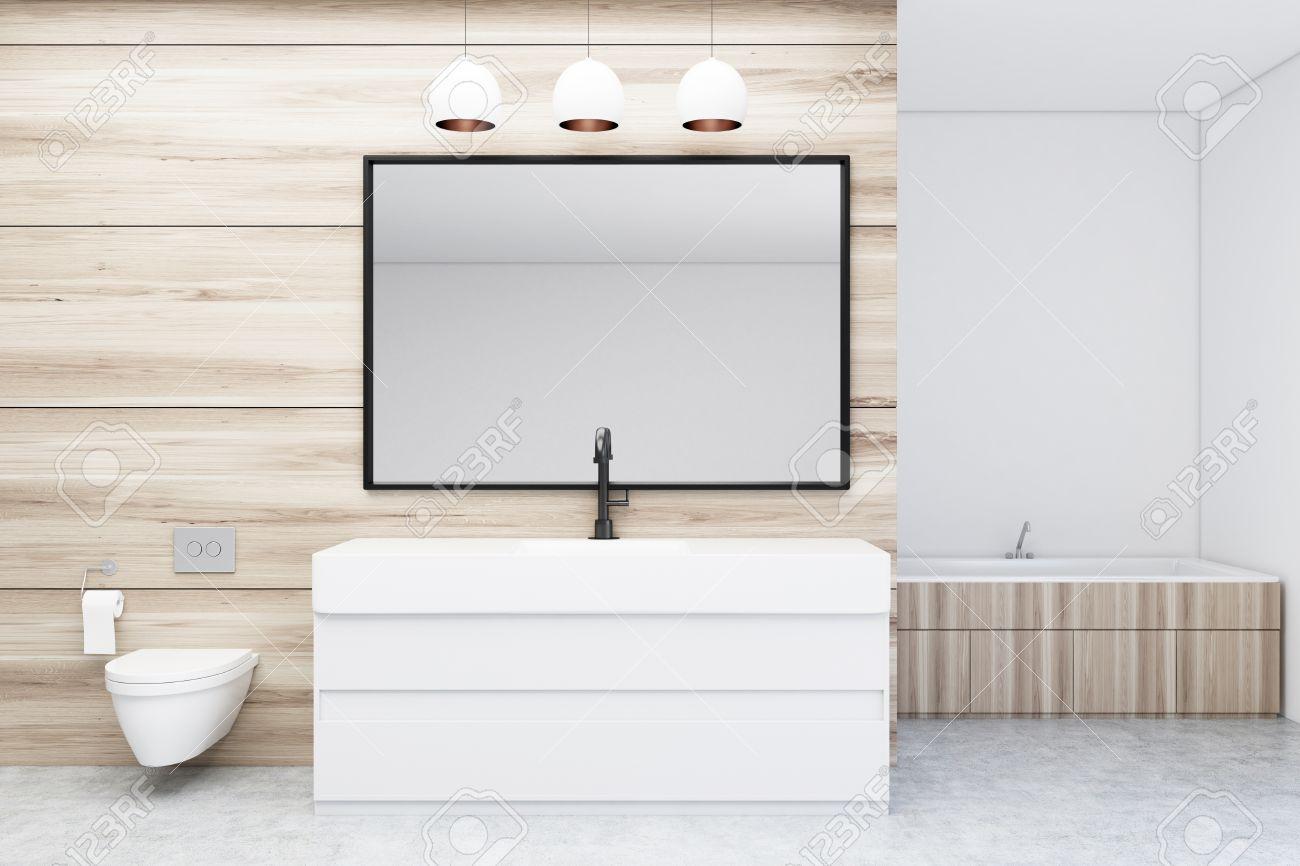 Intérieur moderne de salle de bain avec murs en bois et blanc, sol en  béton, évier, baignoire en bois et toilettes. Grand miroir horizontal. La  ...