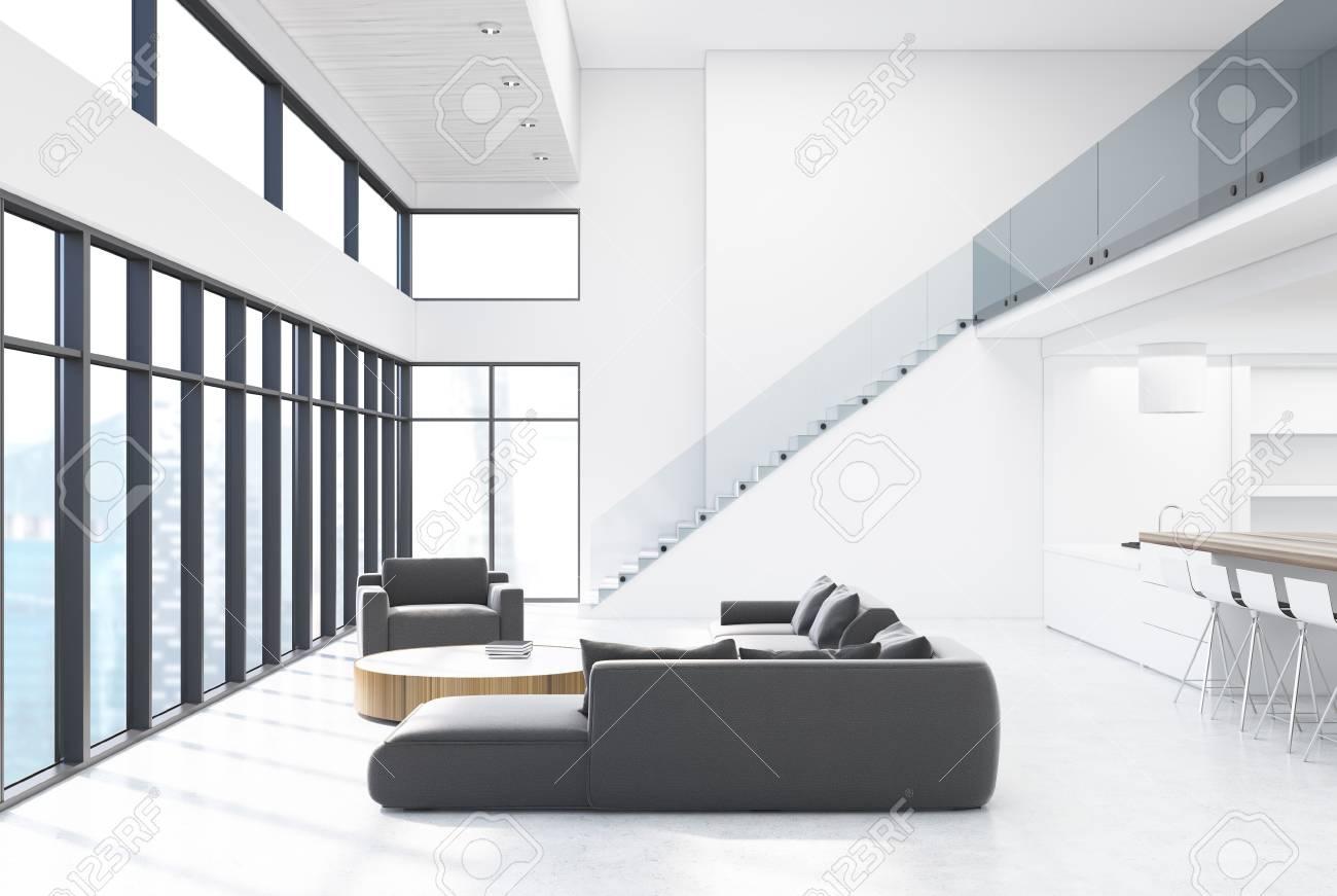 Intérieur de salon blanc avec des canapés gris foncé, un fauteuil, une  table basse ronde et une cuisine sous les escaliers. Maquette 3D