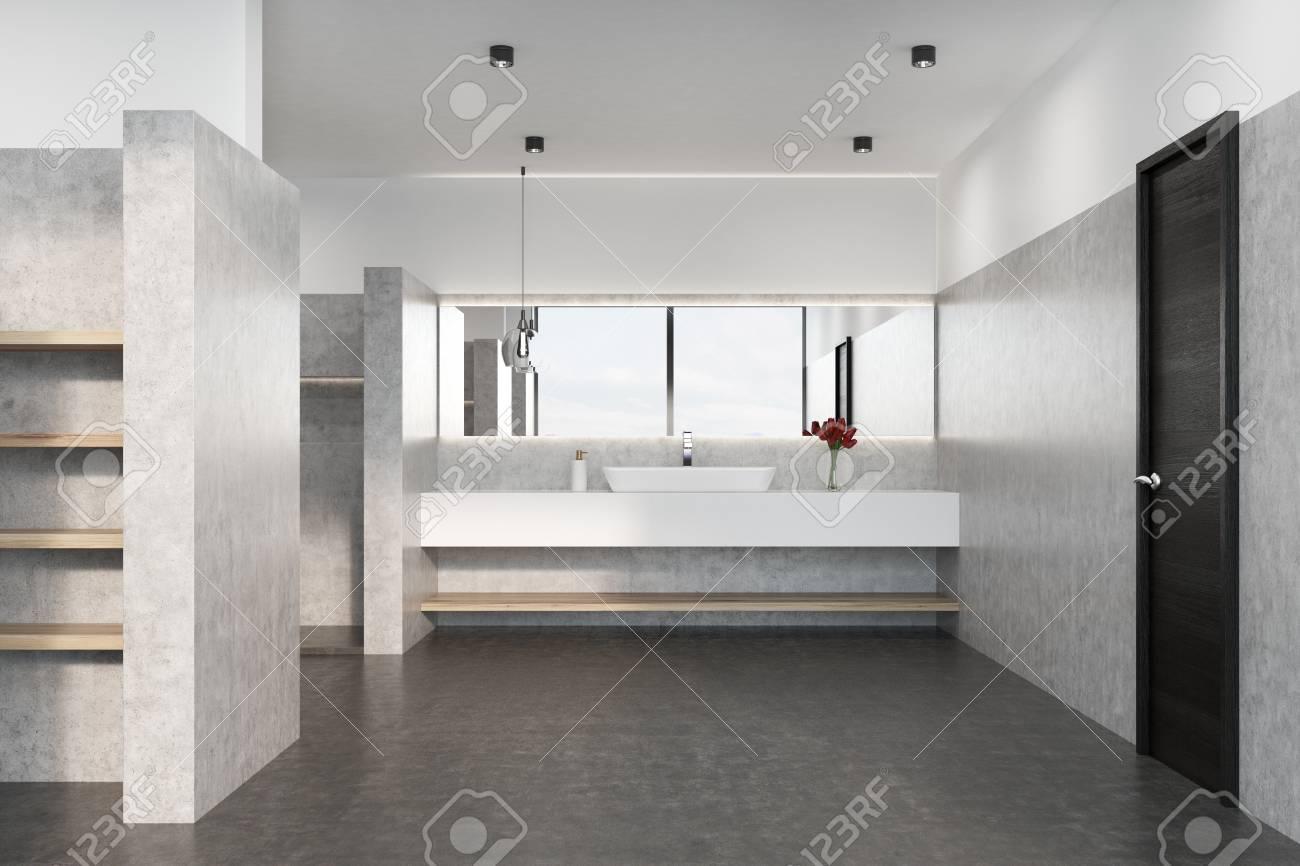 Interno grigio del bagno con pavimento in cemento lavabo in marmo e