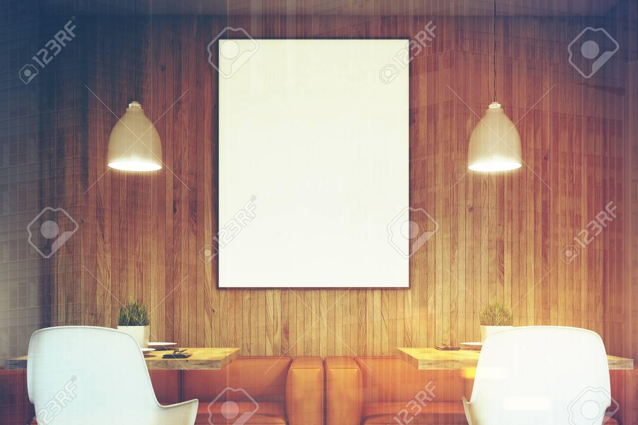 houten caf interieur met twee oranje banken witte stoelen en vierkante tafels verticale ingelijste