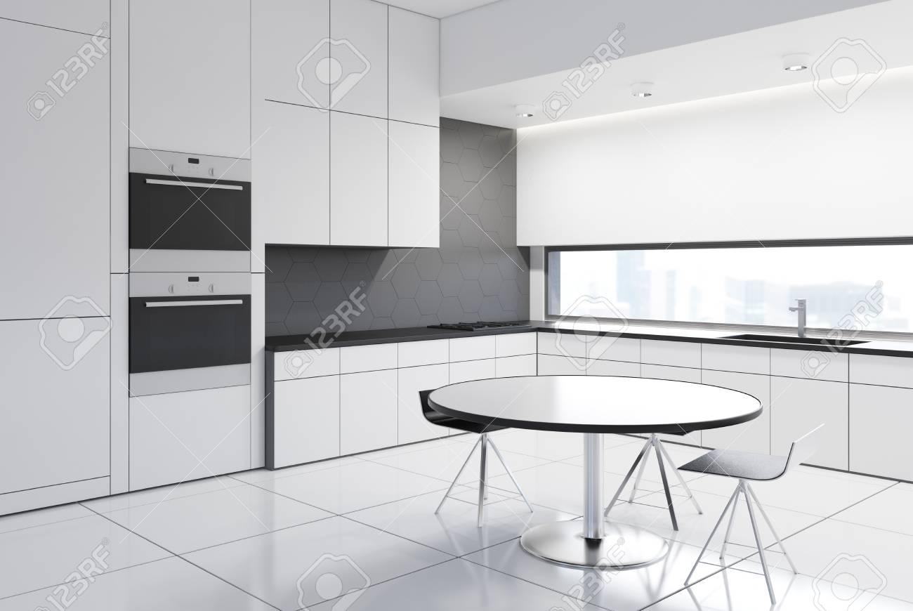 Interni di lusso in cucina bianca con un tavolo rotondo, sedie originali  vicino, costruito in forni e cucine e una lunga finestra. Poster  incorniciato ...