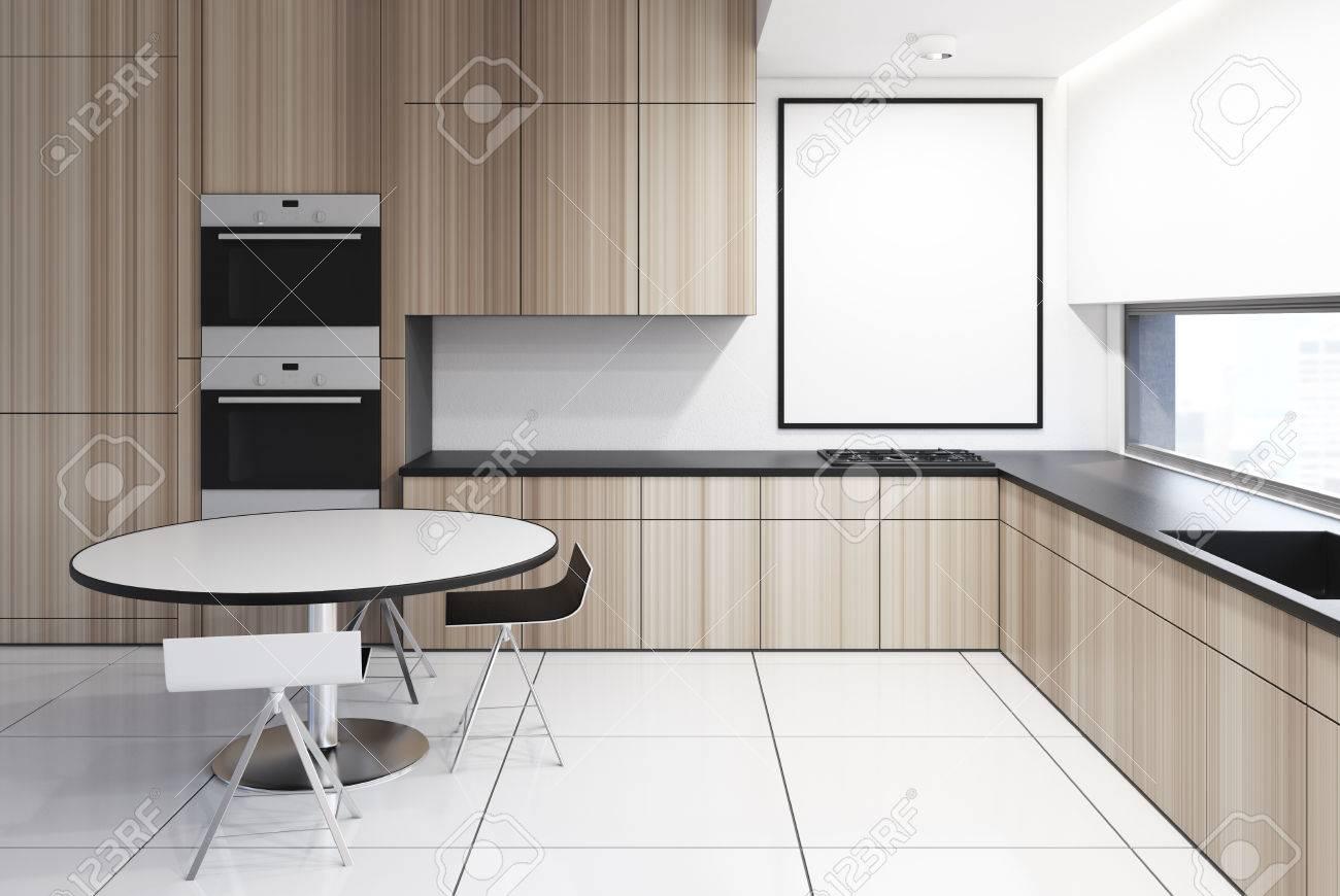 Interno di cucina in legno di lusso con tavolo rotondo, sedie originali in  prossimità, costruiti in forni e fornelli e una lunga finestra. Poster ...