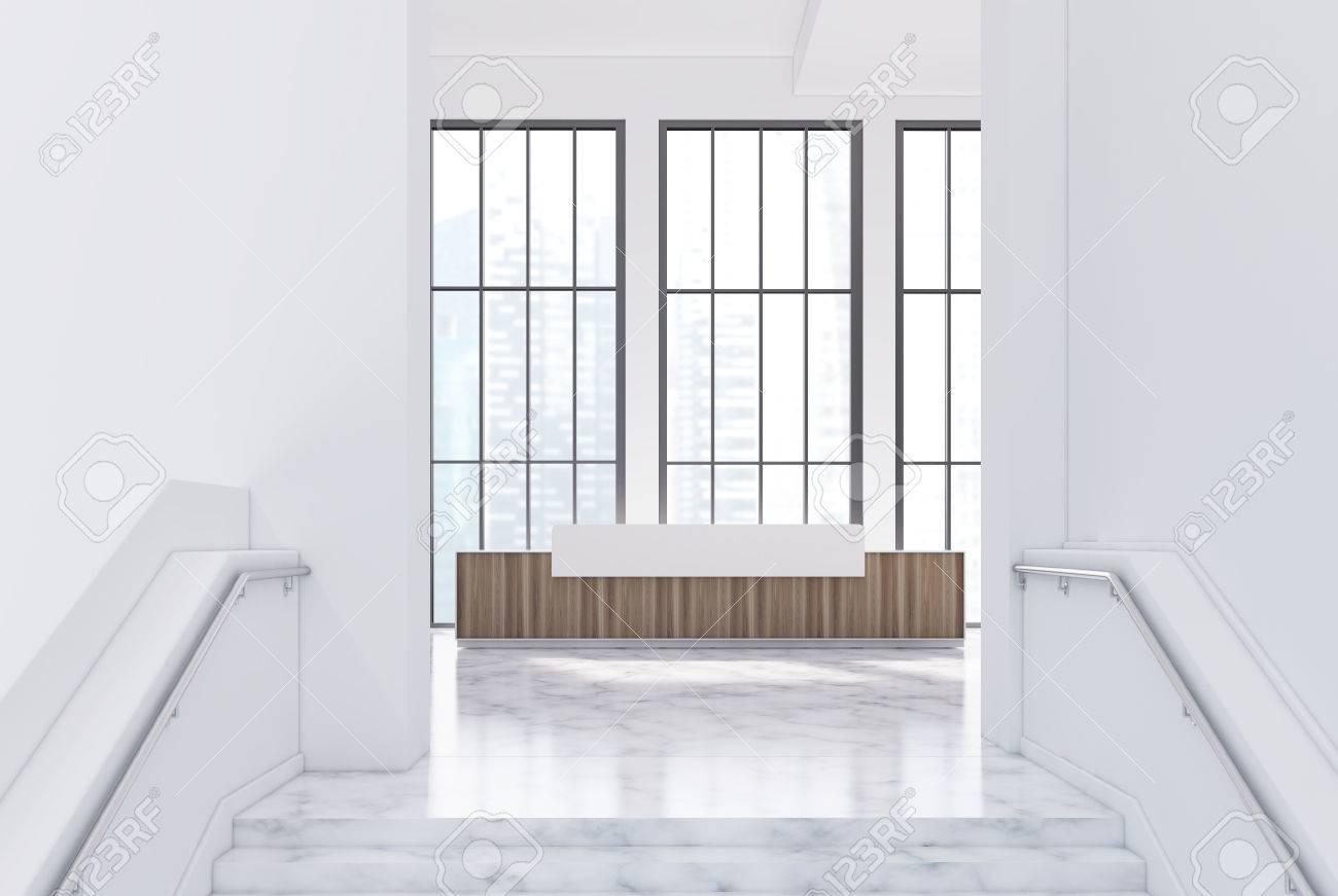 Comptoir de réception blanc et en bois est debout dans une salle