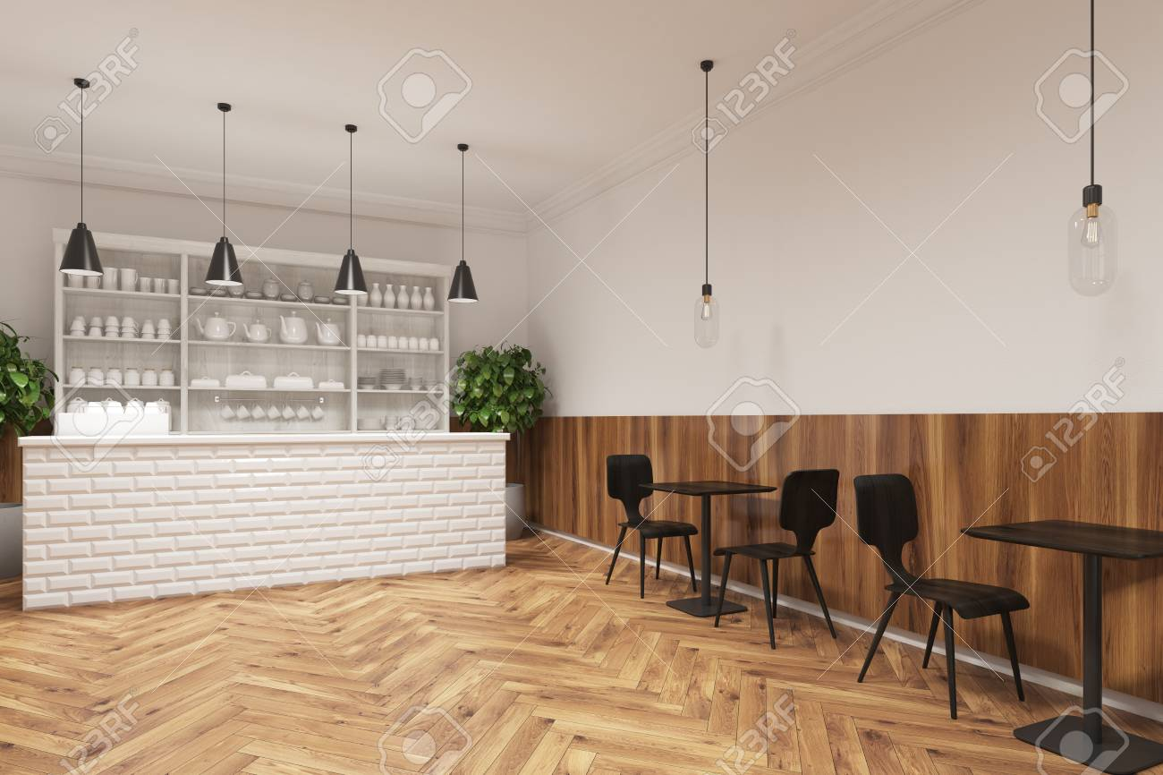 Coffee shop interior black modern chairs standing near square wooden tables and a white bar like counter there is a white cupboard with cups and teapots