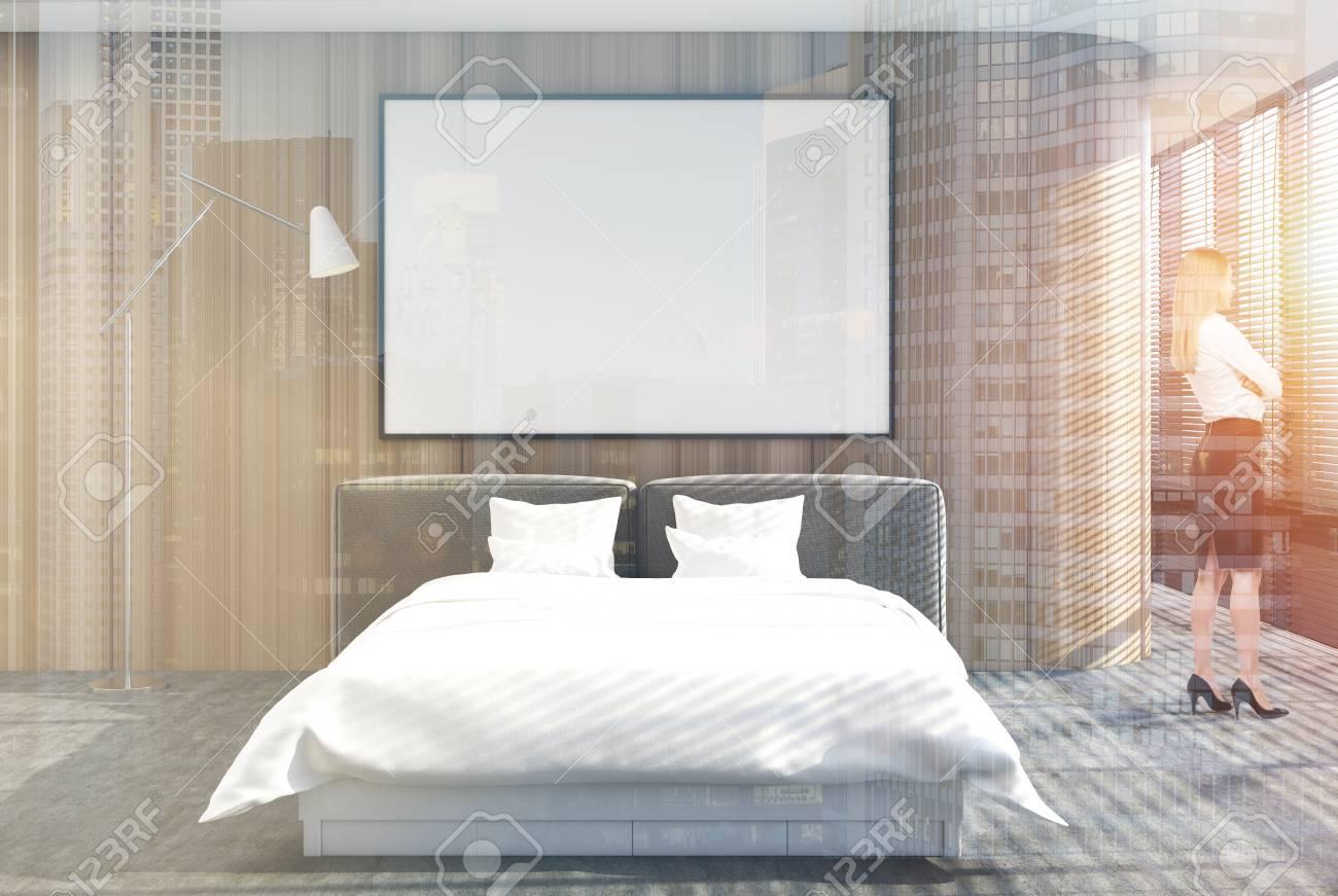 Intérieur de la chambre en mezzanine avec sol en béton, murs en bois, lit  double avec couverture blanche et une affiche au dessus. Rendu 3d maquette  ...