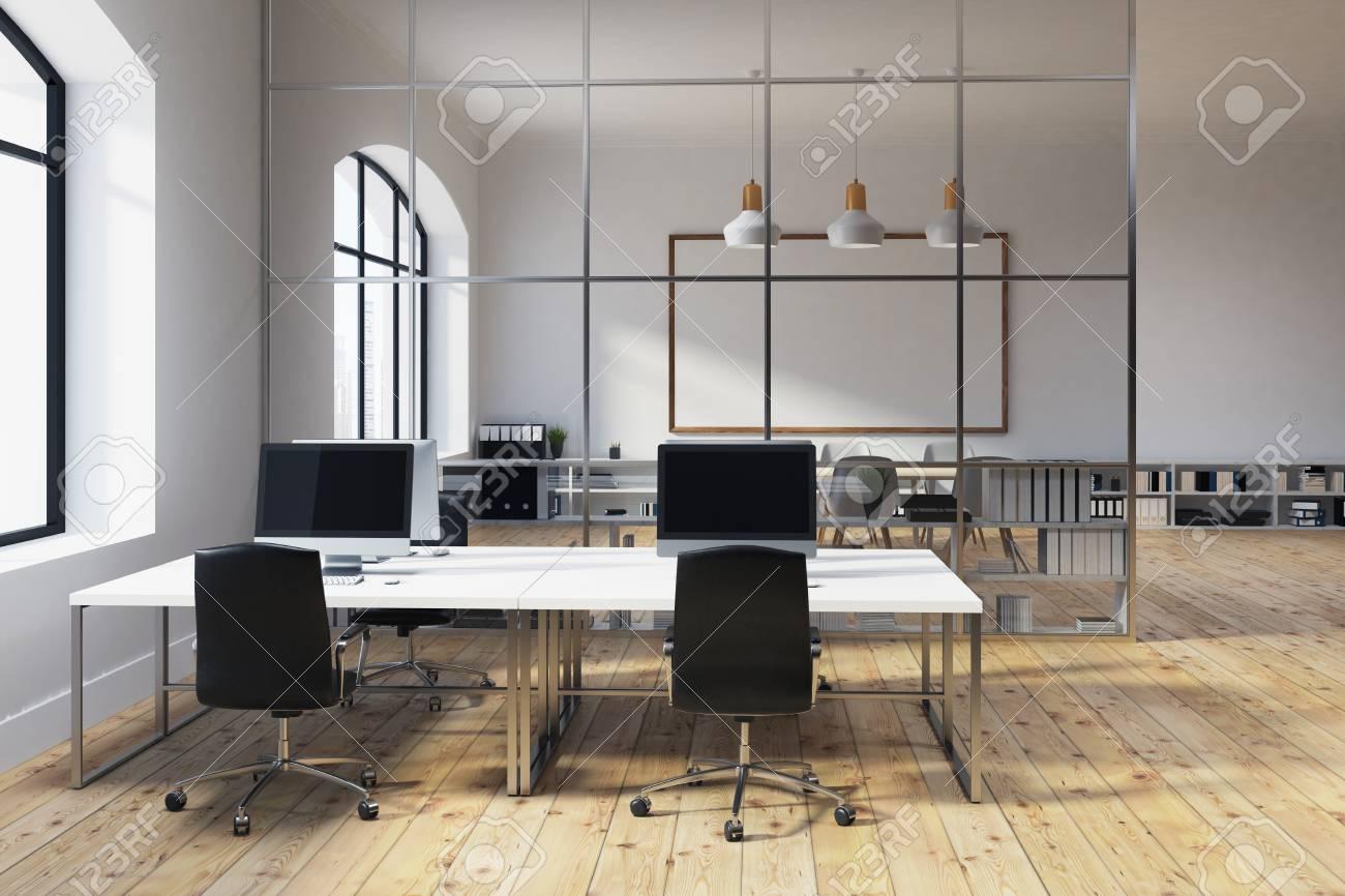 Un espace de bureau blanc à aire ouverte avec une grande fenêtre un