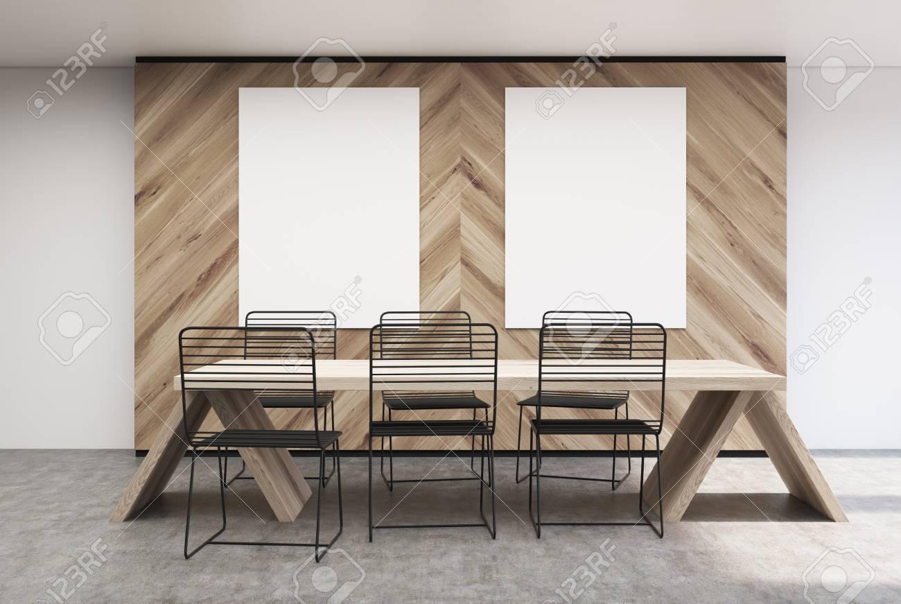 Witte Tafel Zwarte Stoelen.Cafe Of Een Restaurantinterieur Met Witte En Houten Muren Twee Verticale Posters Die Eraan Hangen En Een Massieve Tafel Met Zwarte Stoelen Eromheen