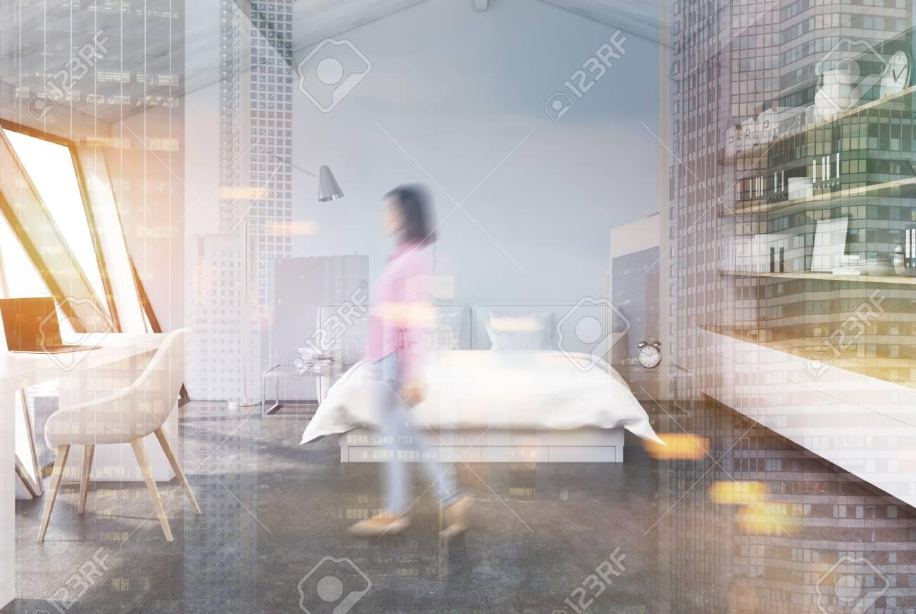Camera Da Letto Bianco E Grigio : Donna in una camera da letto bianca nell attico con un pavimento