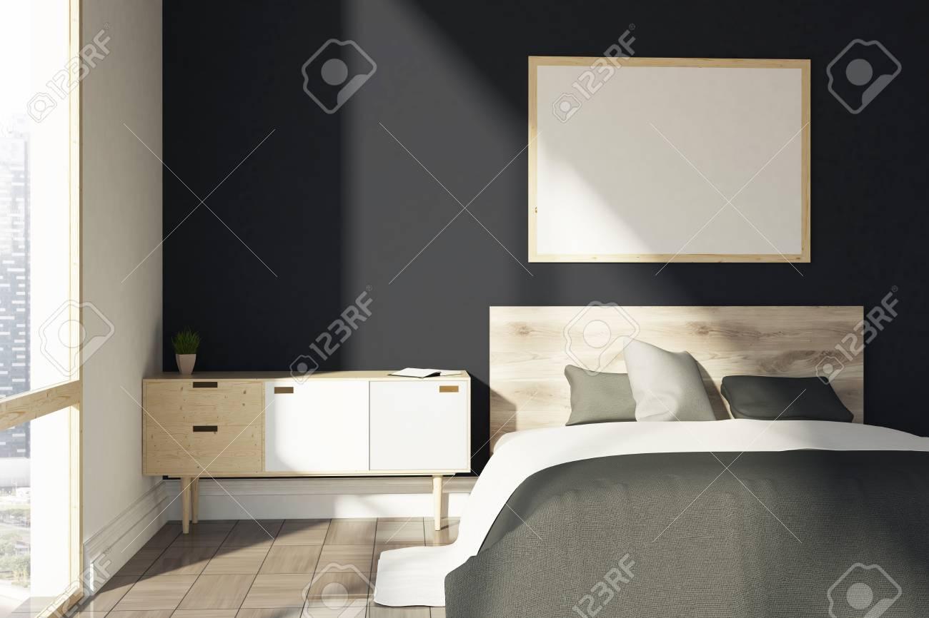 Intérieur de chambre noire avec une couverture grise, un lit double, un  meuble en bois et une fenêtre loft. Une affiche horizontale sur un mur. ...