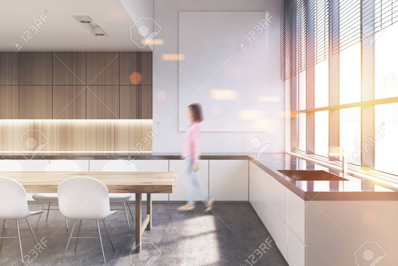 Interior de madera de la cocina con una mesa blanca con sillas, encimeras  de mármol oscuro y una fila de armarios de madera. Mujer. Un cartel  vertical ...