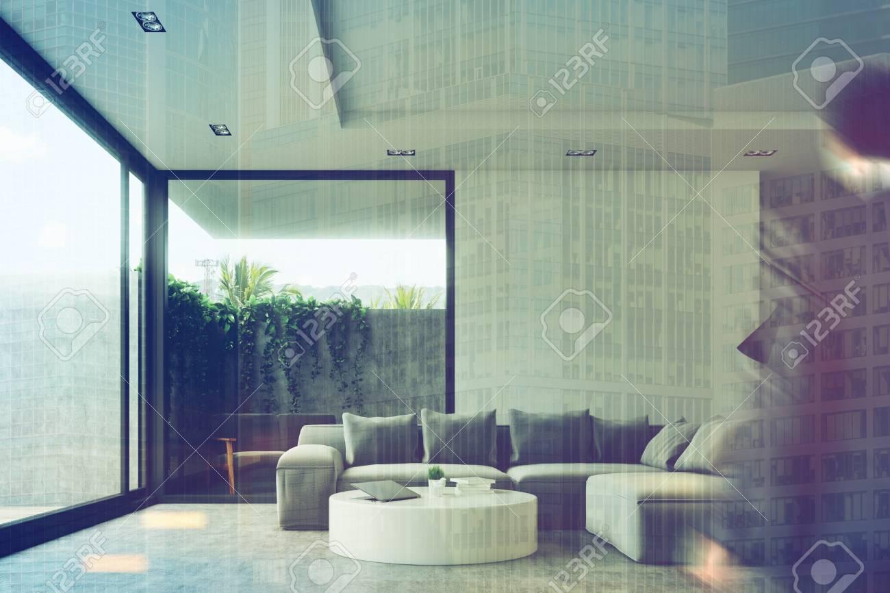 pisos de concreto sala de estar Hombre De Negocios Ini Un Interior De La Sala De Estar Con Un Piso De Concreto Un Sof Gris Una Mesa Redonda Y Una Ventana De Loft Vista Frontal