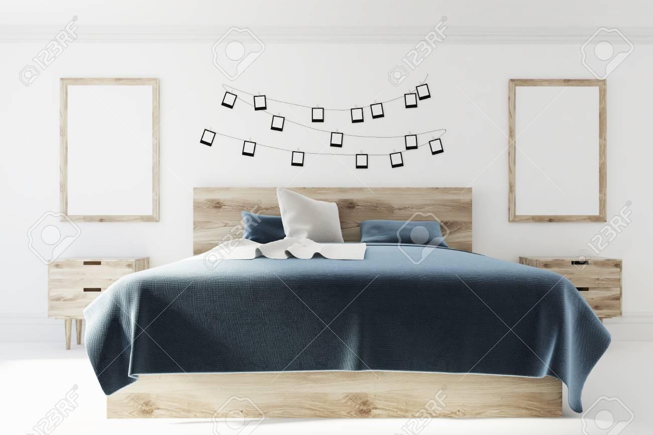 Intérieur De Chambre à Coucher Blanc Avec Une Couverture De Lit Gris Foncé,  Un Lit En Bois Et Des Tables De Chevet Et Deux Affiches Verticales Sur Un  Mur.