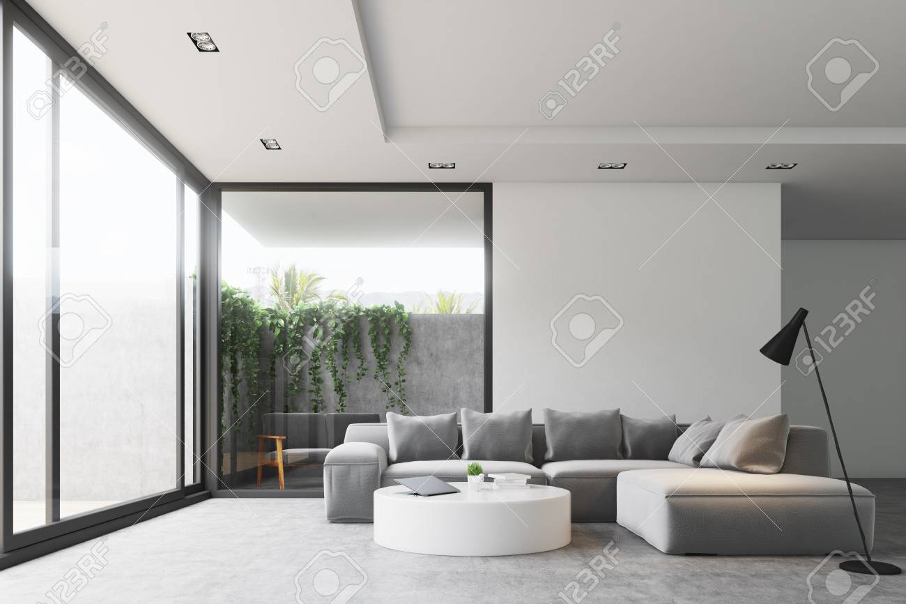 Living Room Interior With A Concrete Floor, A Gray Sofa, A Round Table And