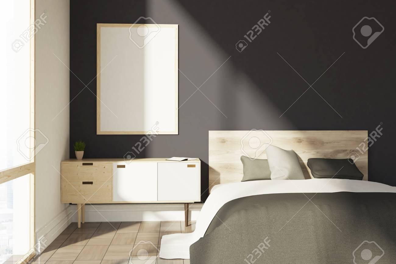 Intérieur de chambre noire avec une couverture grise, un lit double, un  meuble en bois et une fenêtre loft. Une affiche verticale sur un mur.  Maquette ...