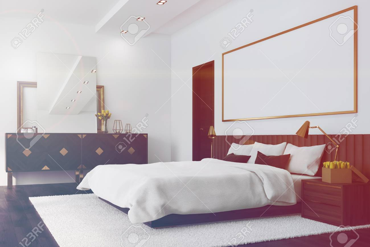 Chambre Blanche Et Bois intérieur de la chambre blanche avec un sol en bois foncé, un grand lit,  deux portes noires et une longue affiche horizontale au-dessus du lit.  coin.