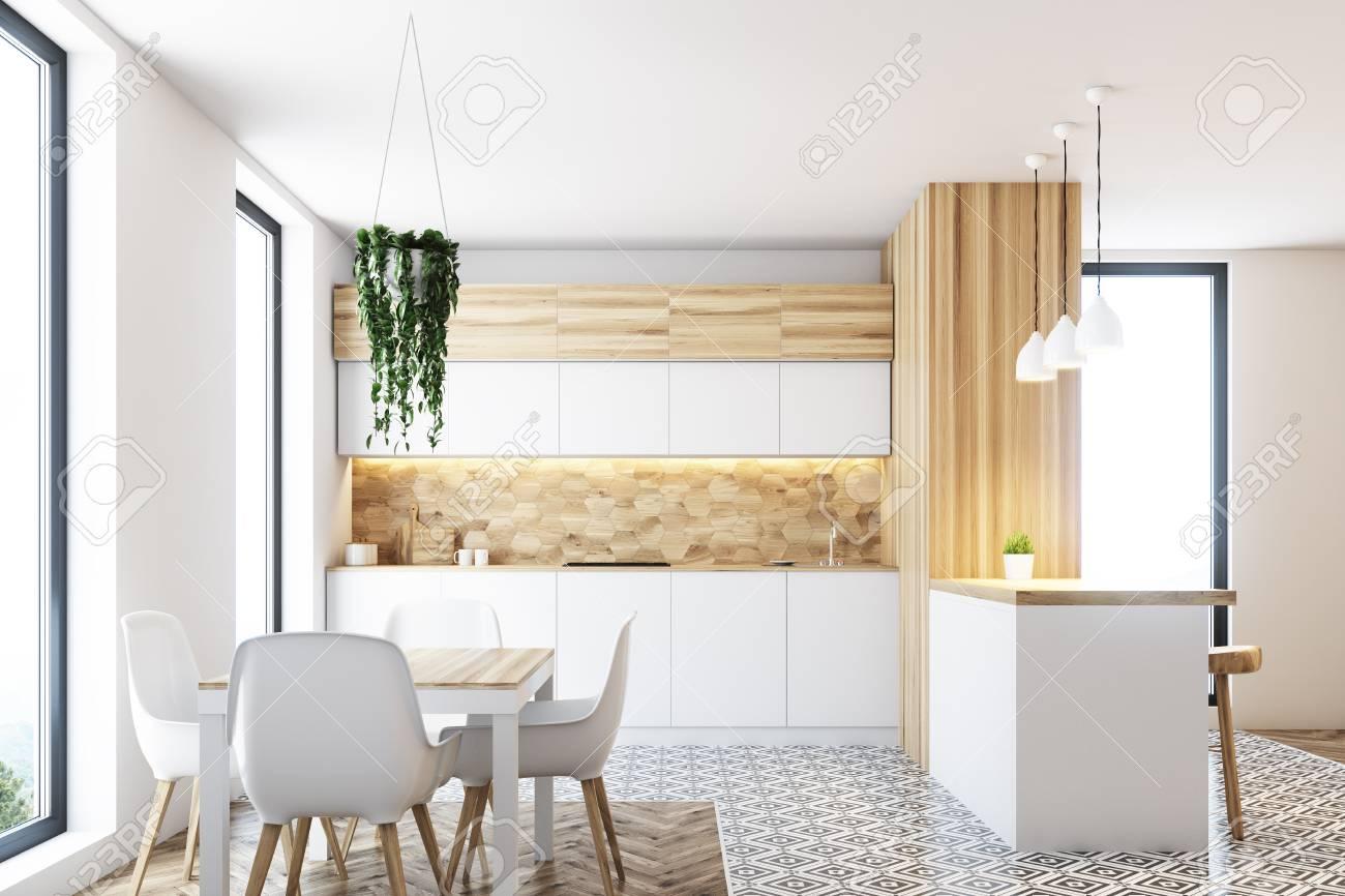 Pared de cocina de patrón hexagonal con encimeras blancas, una barra blanca  y de madera y una mesa con sillas blancas de pie a su alrededor. Simulacro  ...