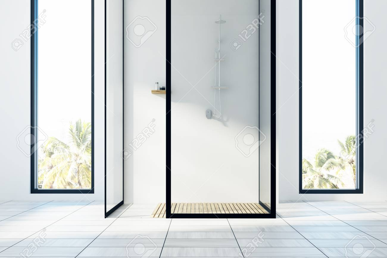 white bathroom interior with a white floor, two narrow and tallstock photo white bathroom interior with a white floor, two narrow and tall windows with a tropical island view and a shower with glass walls