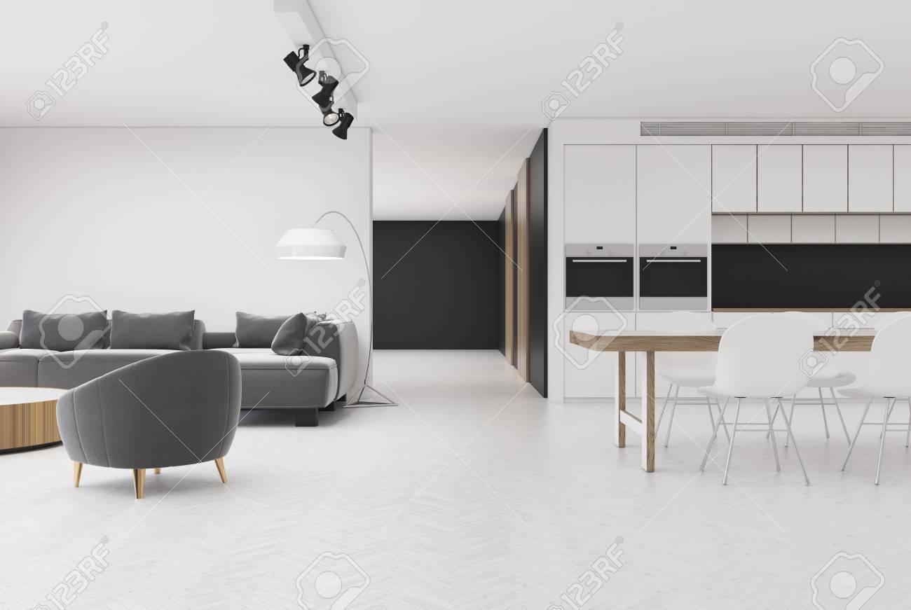 Eettafel Bank En Twee Stoelen.Wit Studio Appartementinterieur Met Een Zachte Grijze Bank Een Leunstoel En Een Keuken Met Twee Ovens En Een Eettafel Met Witte Stoelen Er Omheen