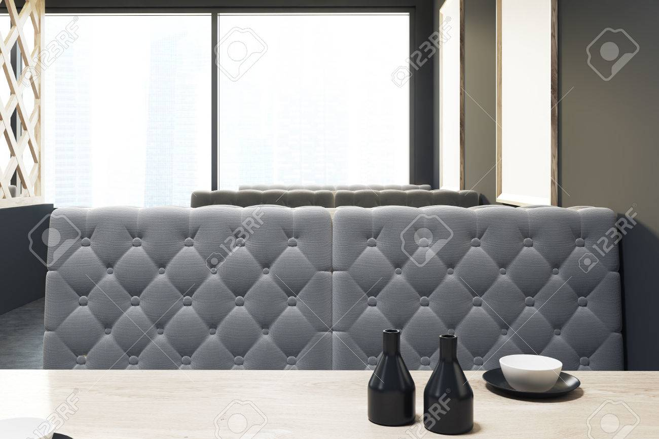 Close Up Of A Loft Cafe Interior With A Wooden Decorative Wall, Soft Gray  Sofas