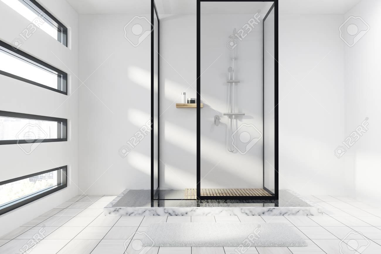 Marbre Blanc Sol Prix gros plan d'un intérieur de salle de bain en marbre blanc et blanc avec un  sol carrelé blanc, des murs de verre et une fenêtre en forme originale.