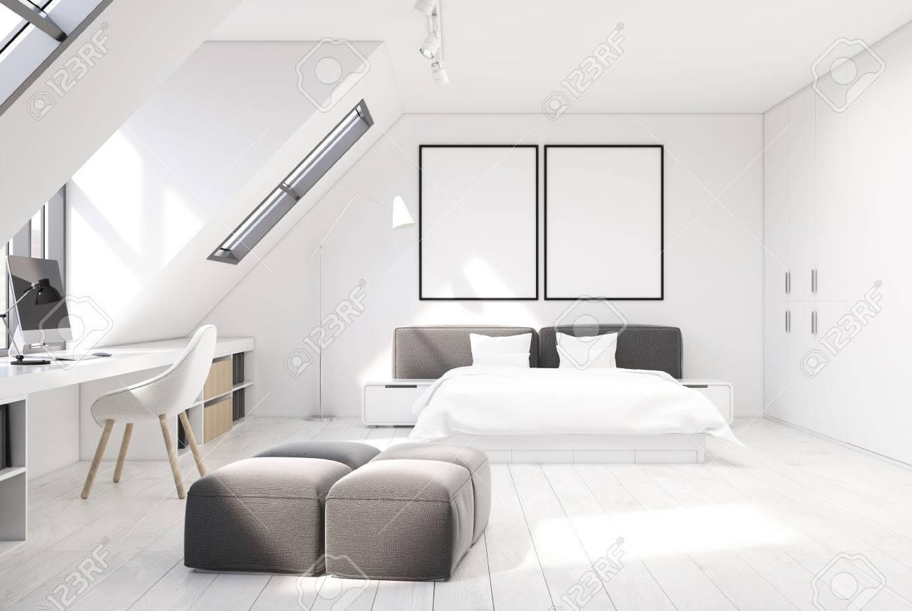 Interno camera da letto con un pavimento in legno bianco e pareti bianche.  C\'è un letto matrimoniale bianco e grigio e una parte ufficio a casa con ...