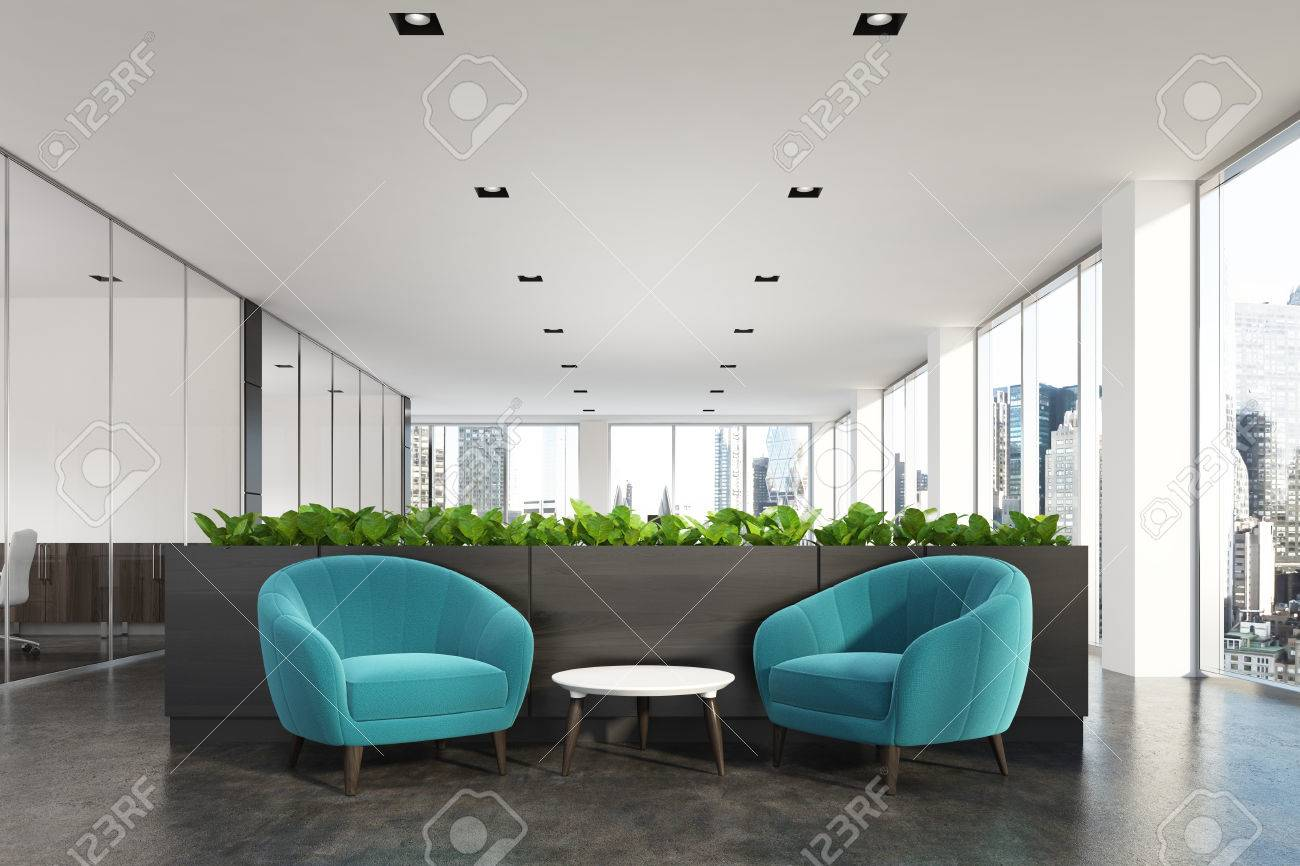 Modern office waiting area with blue armchairs a coffee table