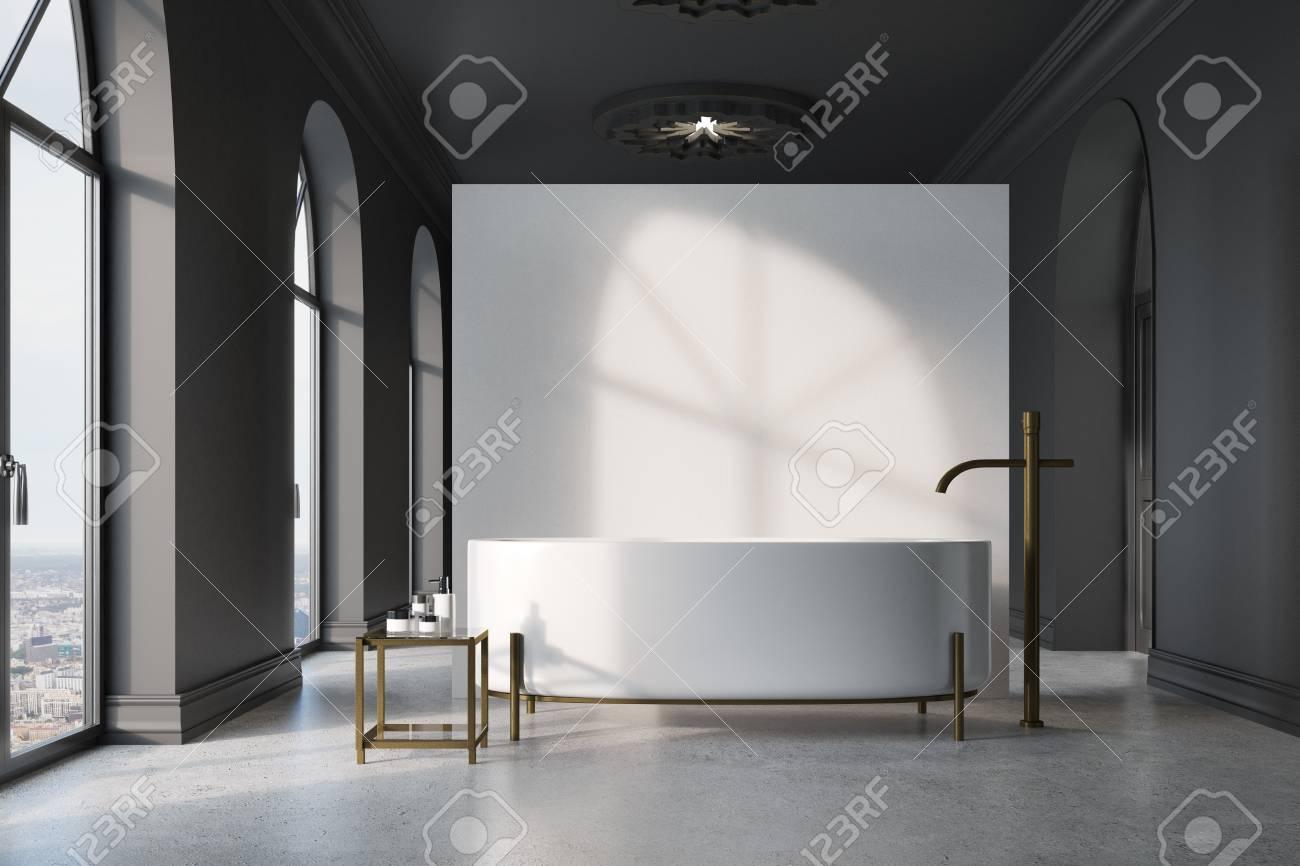 Intérieur de salle de bain gris foncé avec un sol en béton, de nombreuses  fenêtres, une baignoire ronde près d\'un mur blanc et une table avec des ...
