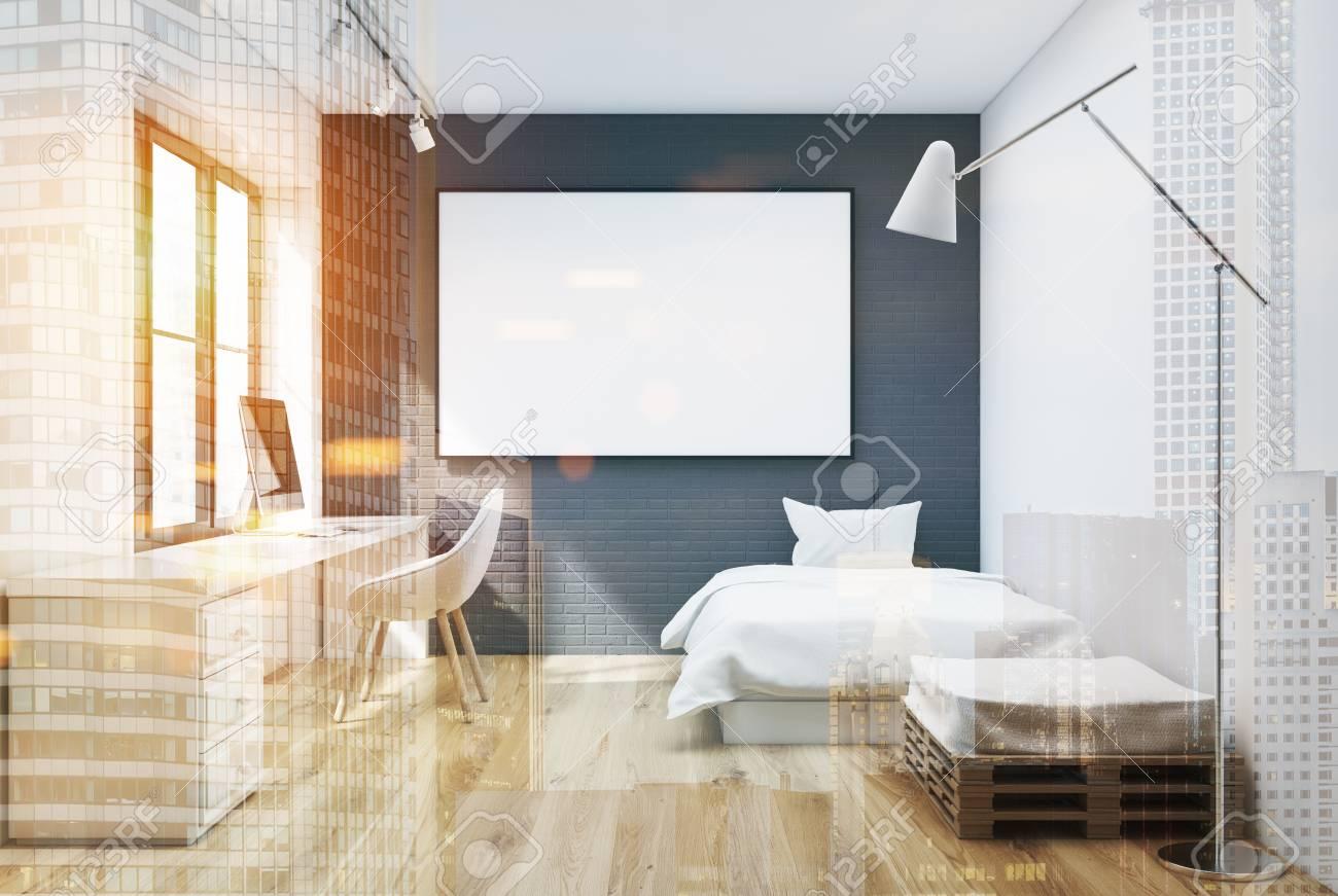 Intérieur gris chambre à coucher en briques avec un lit blanc, un fauteuil  et une table d\'ordinateur. Une affiche horizontale encadrée sur le mur. ...