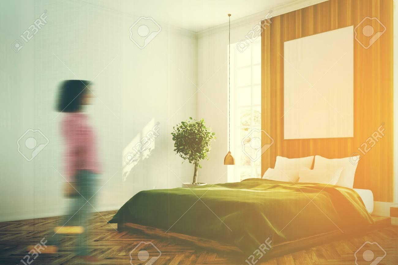 Intérieur de chambre à coucher blanc et en bois avec une grande fenêtre, un  lit vert, un arbre dans une casserole et une table de maquillage avec ...