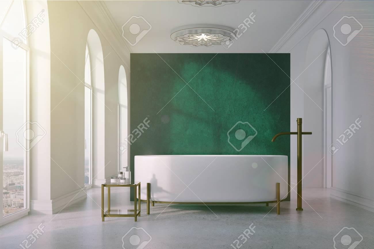 Intérieur de salle de bain vert et blanc avec un sol en béton, de  nombreuses fenêtres, une baignoire ronde près d\'un mur vert et une table  avec des ...