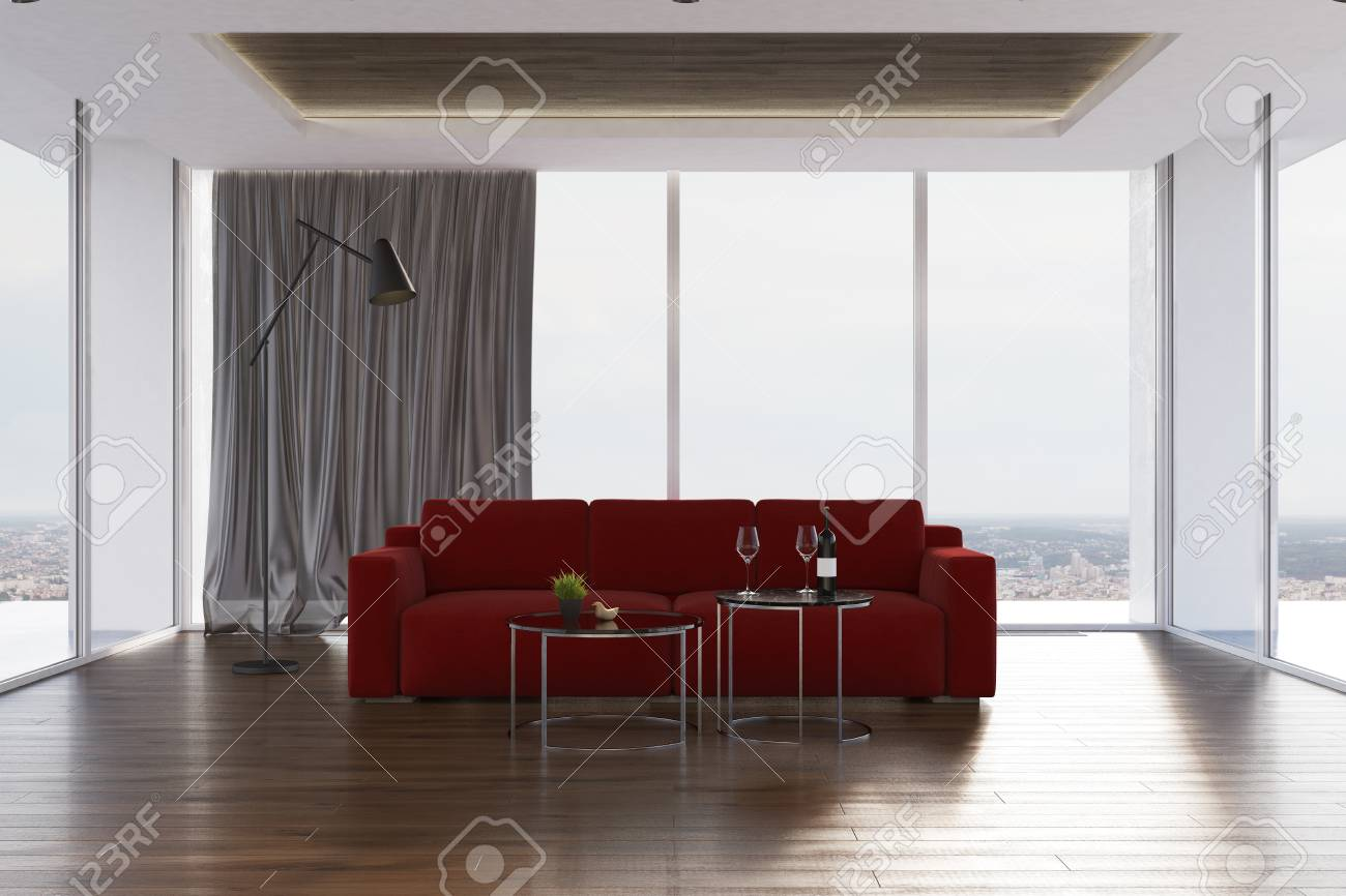 Loft living room interior with a wooden floor, a dark red sofa..