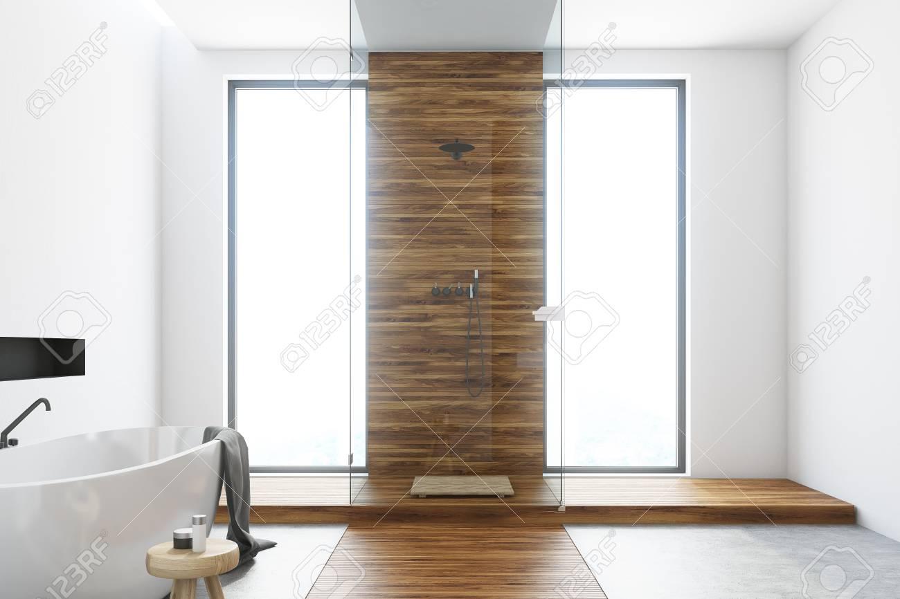 Intérieur de salle de bain blanc et en bois avec un plancher en bois, de  grandes fenêtres, une baignoire ronde blanche et une douche avec des parois  ...