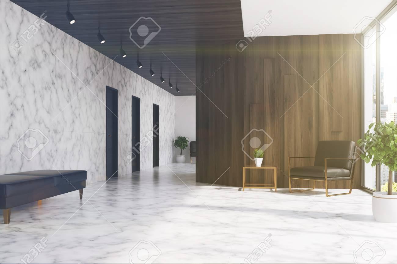 Salle d ascenseur en marbre blanc et bois sombre dans un bureau