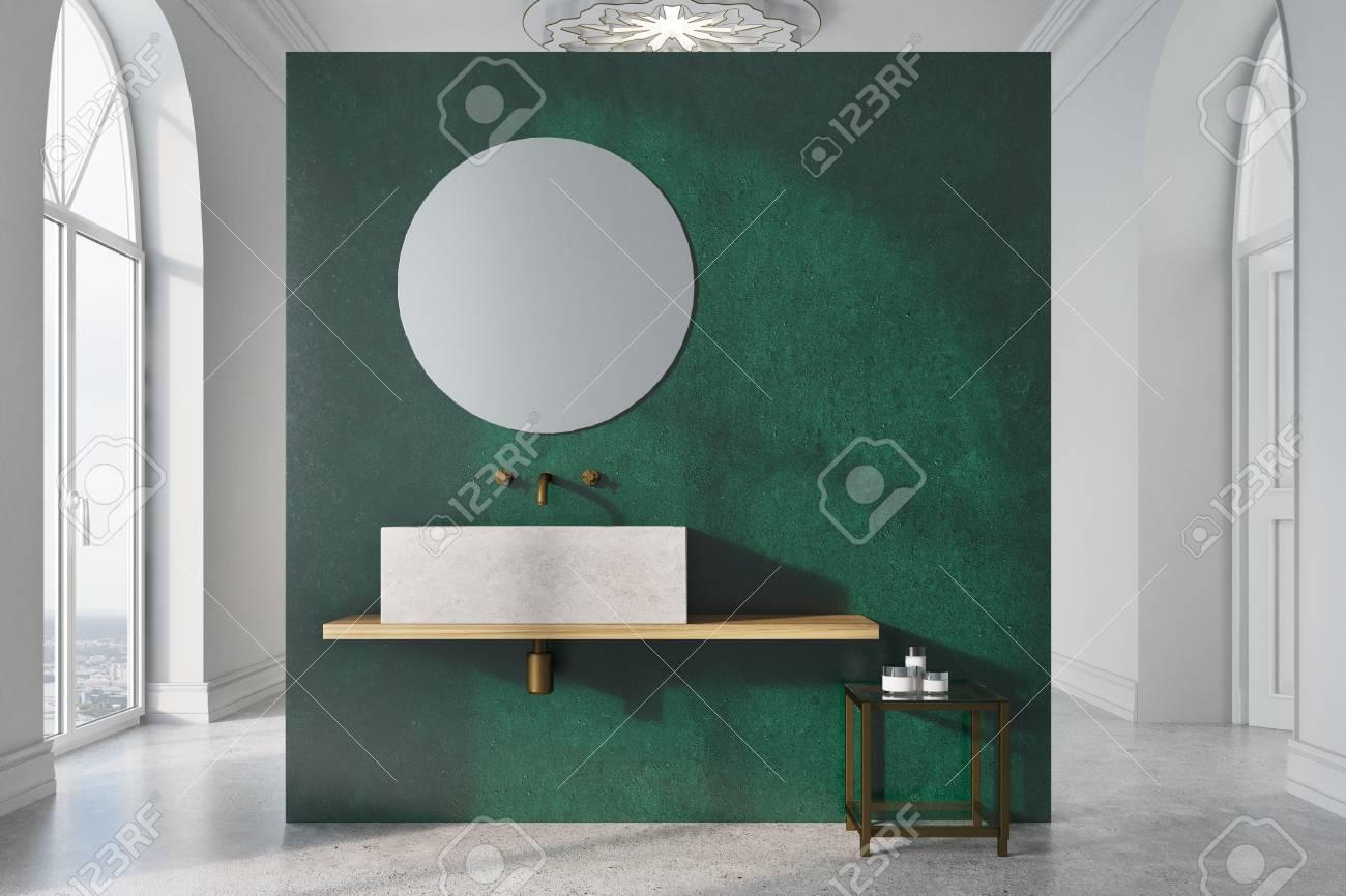 Intérieur de salle de bains vert et blanc avec un sol en béton, de  nombreuses fenêtres, un miroir rond, un évier angulaire près d\'un mur vert  et une ...