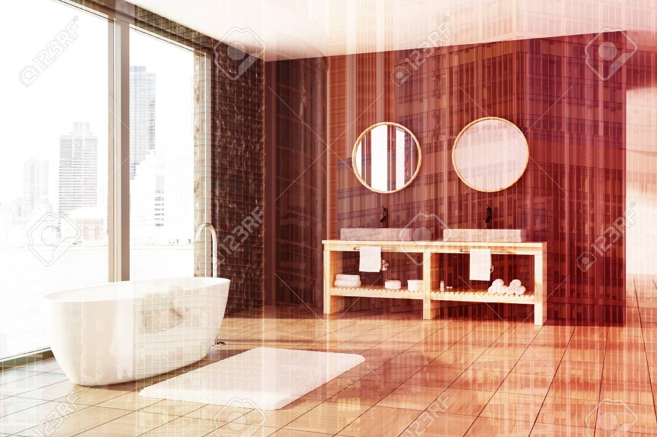 Interni del bagno in pietra con marmo nero e pareti in legno, una vasca  bianca, un doppio lavandino e una finestra panoramica. Rendering 3d imitare  in ...