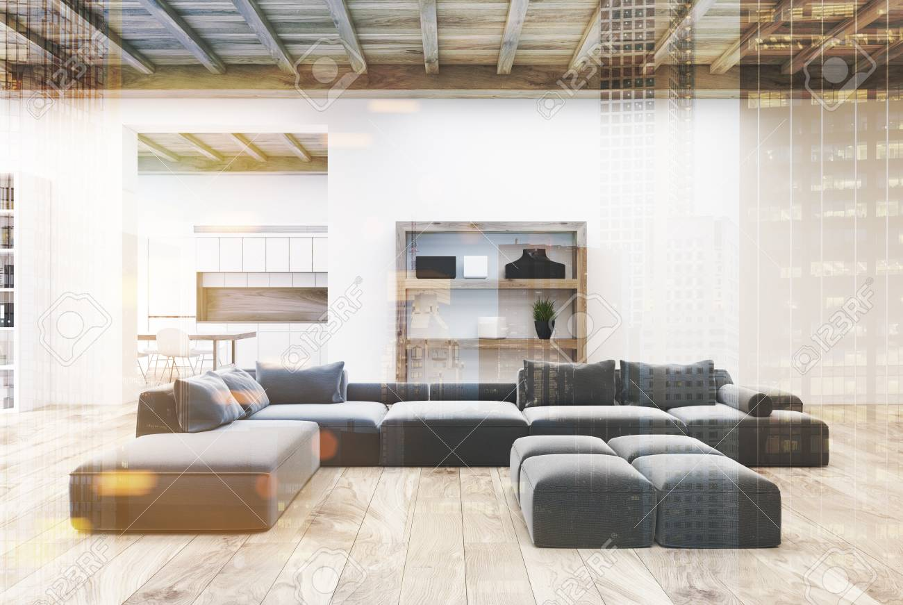 Interiore bianco del salone con un pavimento di legno, mensole, parecchi  sofà grigi e una cucina nella priorità bassa. Derisione di immagine tonica  di ...