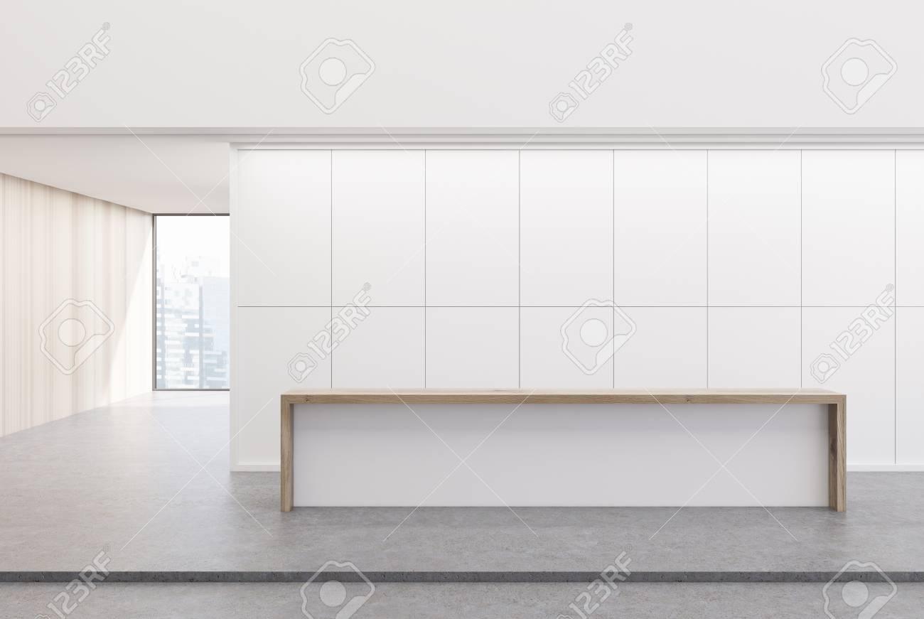 Reception Ufficio Legno : La reception bianca e in legno è in piedi nella hall di un ufficio