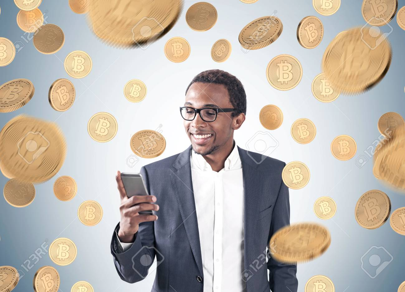 Portrait of a young smiling African American businessman wearing a suit and a shirt and looking at his smartphone screen. Gray background, a bitcoin rain - 87986531