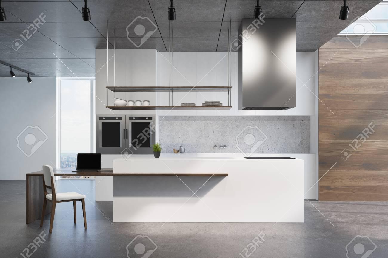 Comptoir De Cuisine Blanc Et En Bois Debout Sur Un Sol Gris Foncé Dans Une  Pièce Avec Des Murs En Bois Et Blancs Et Des Fenêtres De Loft.